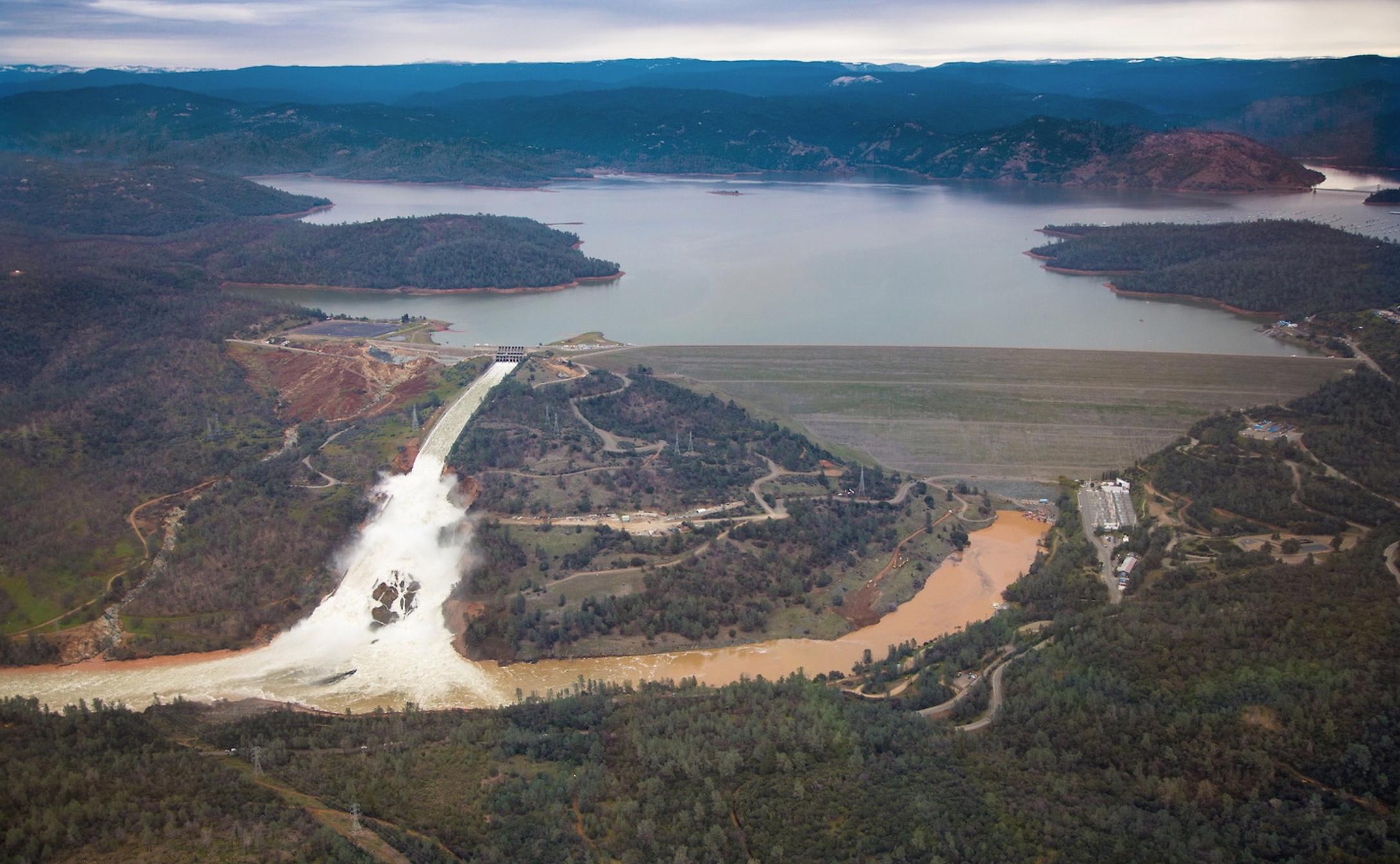 Le barrage à droite, l'évacuateur endommagé au centre et l'évacuateur d'urgence à gauche